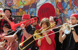 Horns of Plenty play in front of the mural featuring Horns of Plenty playing at Carnival